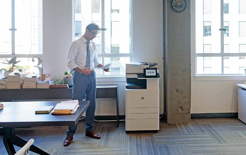 mężczyzna w biurze z urządzeniem drukującym